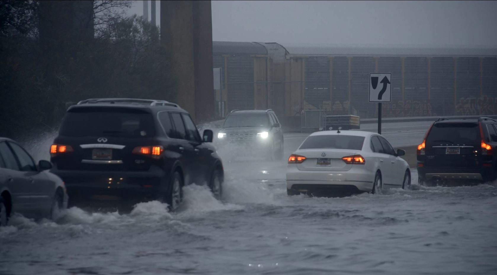 Traffic driving through high water in a city.