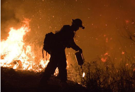 Fire crews set back-burn fires in an attempt to halt the advance of a Southern California fire in 2007. (Credit: Andrea Booher, FEMA)